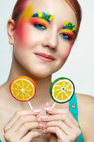 Teenager girl with unusual face art make-up and with lollipops in hands.