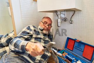 Klempner bei Reparatur vom Waschbecken Abfluss