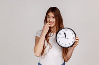 Portrait of nervous dark haired woman biting nails holding big wall clock, deadline, need hurry up.
