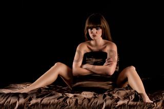 Frau sitzt im Bett in brauner Seidenbettwaesche