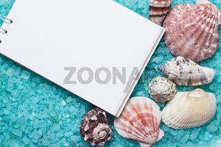 notebook over blue bath salt and seashells background