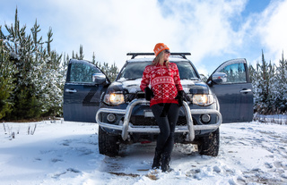 Woman standing in front of 4wd in snow among young pine forest