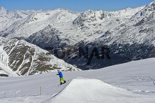 Snowboarder auf einem Sprunghügel im Skigebiet von Saas-Fee