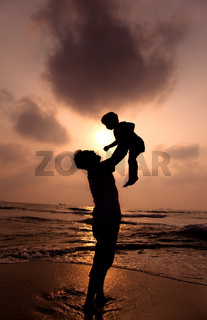 the silhouette of happy father and little girl on the beach