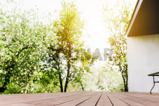Sun rays on blurred view from wooden deck on balcony