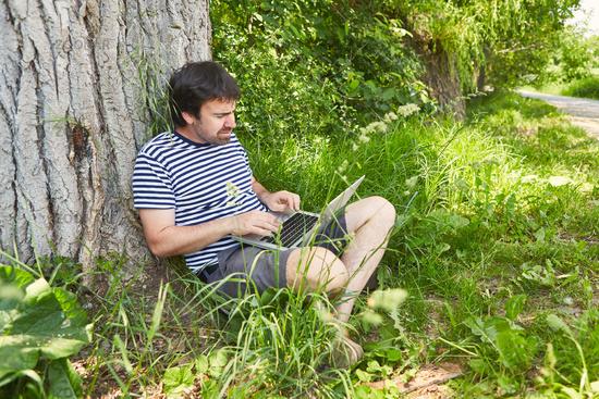 Mann als Programmierer am Laptop PC im Garten