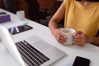 Midsection of caucasian businesswoman sitting at desk using laptop and holding cup of coffee