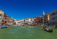 VENICE, ITALY - AUGUST 22, 2016: Tourists ride in gondola near Rialto bridge on August 22, 2016 in Venice Italy