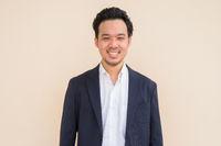 Portrait of happy Asian businessman wearing suit against plain background