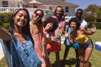 Portrait of diverse group of friends taking selfie at a pool party
