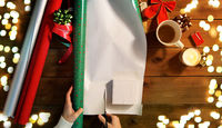hands wrapping christmas gift into paper at home
