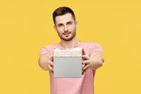 Handsome young man giving gift box looking to camera on yellow studio background