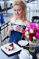 a beautiful young blond girl in summer dress at the table in pavement cafe