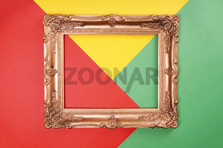 empty gold frame on color paper background in red green and yellow