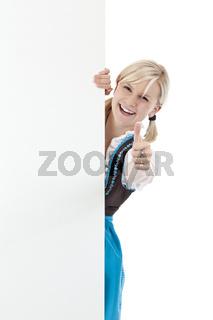 hübsches blondes Mädchen im Dirndl zeigt Daumen u. hält Werbeschild