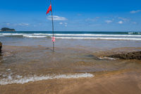 Red flag on the beach. Swimming and surfing ban.