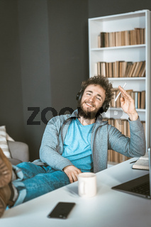 Happy student at home. Remote learning the concept. A young man with headphones smiles sitting in front of a computer.