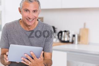 Happy man using his digital tablet
