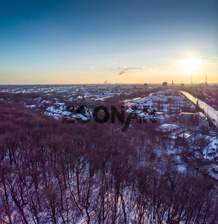 View of the snow-covered skyline of Duisburg at sunset from above