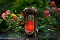 Grablaterne aus Metall vor Blumen auf einem Grab