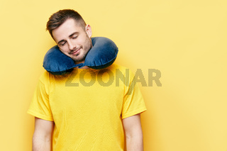 Young man with closed eyes resting on travel pillow over yellow background