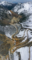 aerial view of the winding dirt road in snow mountains