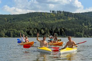 Waving cheerful friends in kayaks summer