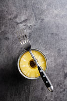 Canned sliced pineapple fruit in can with fork