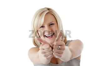 Hübsche blonde Frau hält lächelnd beide Daumen nach oben