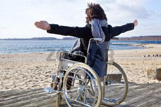 Frau im Rollstuhl am Strand