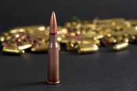 Copper machine gun bullet, more blurred yellow ammo on black board background