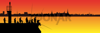 Silhouettes of fishermen with fishing rods on pier with lighthouse and long city skyline on background of sunset. Lots of people with long fishing rods with copy space.