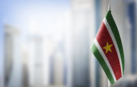 A small flag of Suriname on the background of a blurred background