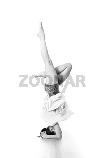 Portrait of beautiful elegant slim active sporty young woman practicing standing on head yoga pose in yoga studio. Healthy active lifestyle. Artistic black and white image.