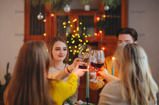 Happy young friends clinking glasses of wine over table decorated for Christmas celebration