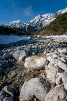 Clear mountain river flowing over stones through evergreen forest, Mieminger Plateau, Tirol, Austria