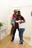 Happy african american father embracing with son and daughter in hallway at home