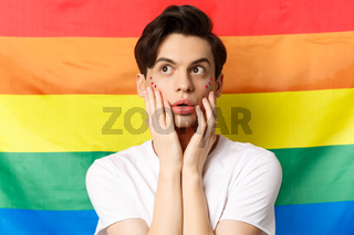 Portrait of sensual and beautiful gay man with glitter makeup on face, looking at upper left corner excited, standing against lgbtq rainbow flag