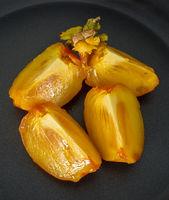 Aufgeschnitten reife saftige Sharonfrucht auf schwarzem Hintergrund