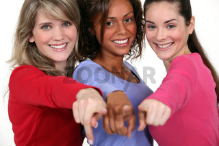 Three friends pointing at the camera.