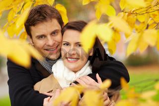 Paar im Herbst zwischen Blättern