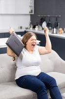 Fury, rage, anger with laptop in hand young overweight girl staying at home during quarantine. Self isolation as prevention. Work distantly concept. Facial expressions, emotions, feelings