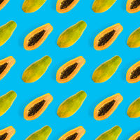 Fresh ripe papaya seamless pattern on blue background. Tropical abstract background. Top view.