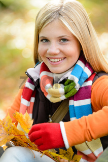 Smiling young girl autumn colorful scarf leaves