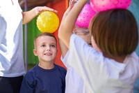 Kinder beim Ball spielen draußen vor dem Kindergarten