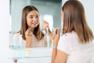 teenage girl with floss cleaning teeth at bathroom