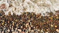 Wellen spülen Wasser über Steine und Kiesel am Strand