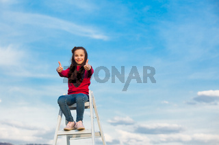 the girl on top of a ladder against the sky