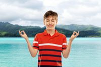 happy smiling meditating boy over hills and ocean