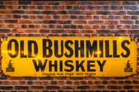 Old Bushmills Whiskey famous for over 300 years sign on rustic brick wall